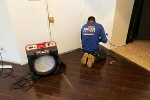 Air scrubber in water damaged room with baker roofing & construction worker