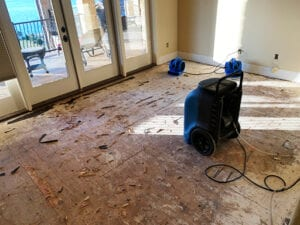 Dehumidifer and air movers set up in water damaged room