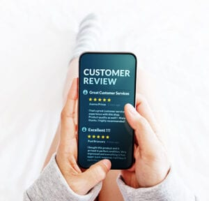 woman holding cell phone looking at company reviews